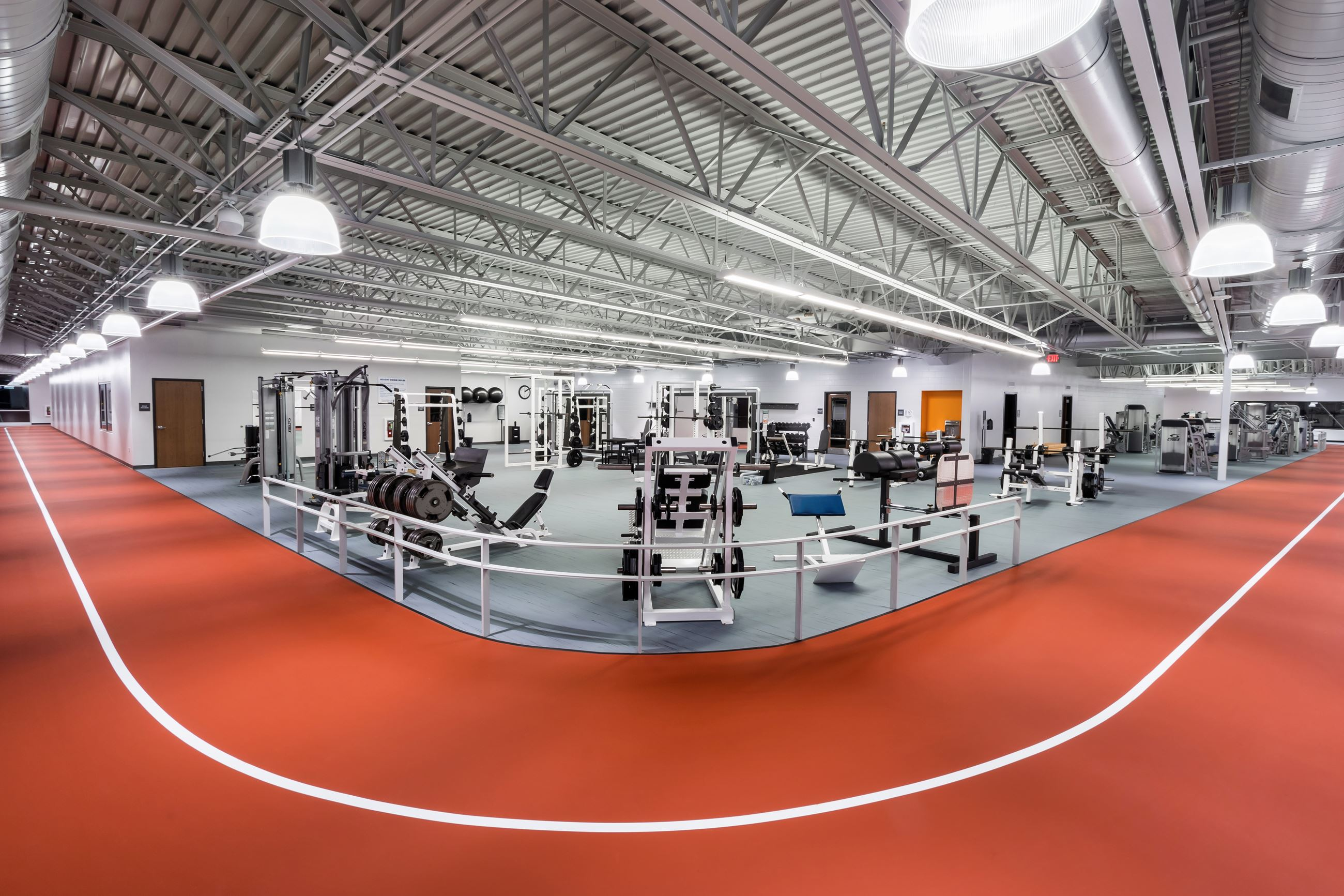 An indoor track alongside a workout area in a large indoor fitness facility